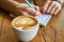 tomando notas junto a taza de café